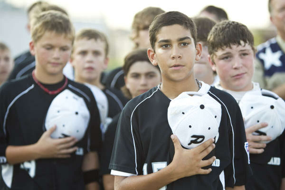 Jorge Gutierrez listens to the national anthem as he and fellow members of the Pearland Little League team are honored Sunday at Pearland ISD Stadium during a pep rally and fundraising event to help them pay for their trip.