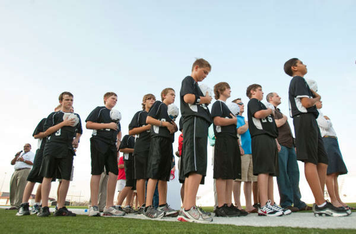 Jake Orlando, center, and the rest of the Pearland Little League team observe the national anthem during Sunday's pep rally and fundraising event.