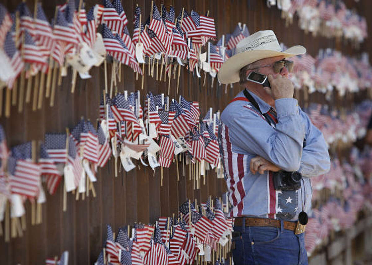 David Walker, a rancher, stands at the border wall with Mexico on Sunday in Hereford, Ariz.