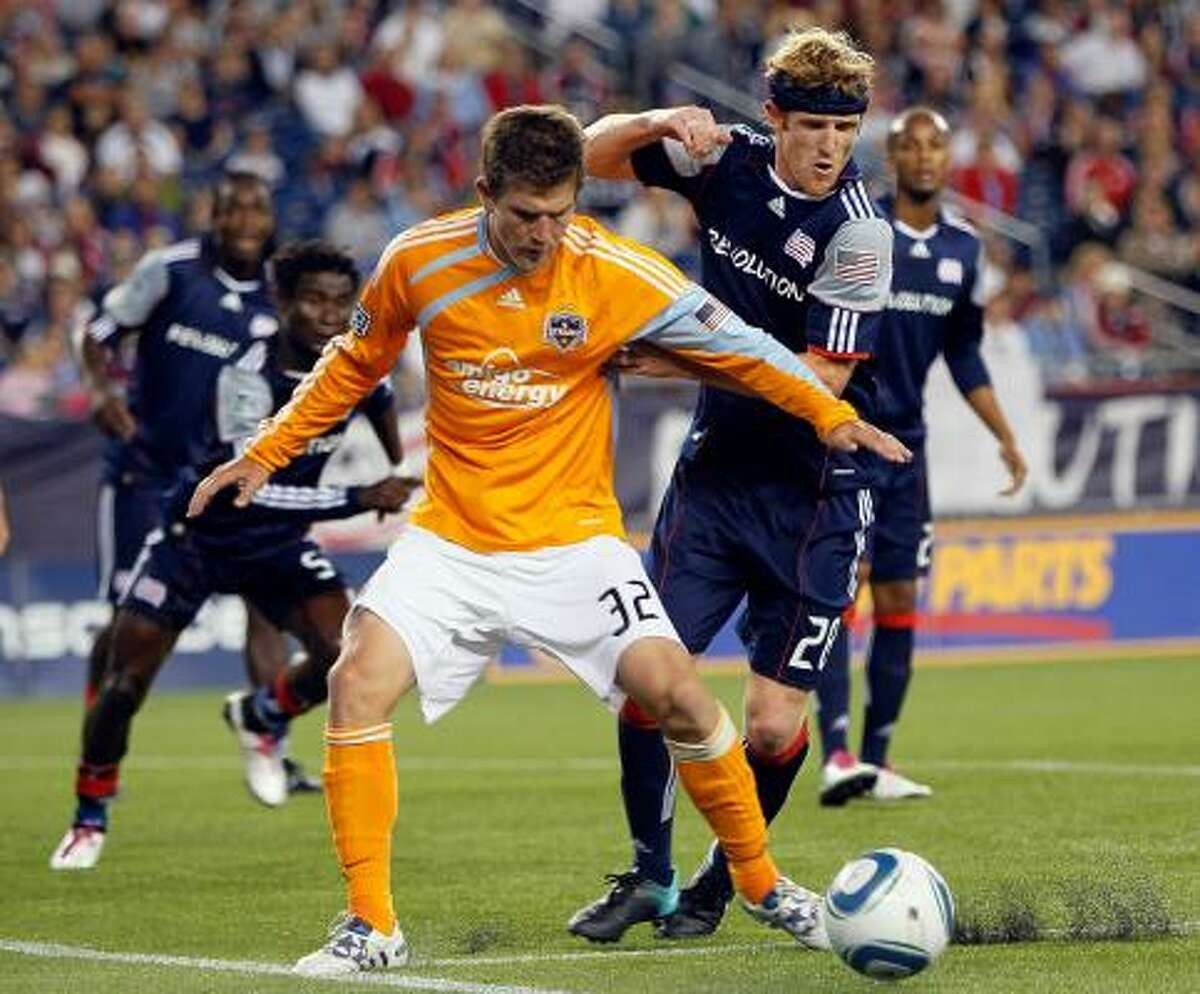 New England's Pat Phelan, right, tries to keep Dynamo defender Bobby Boswell away from the Revolution's net.
