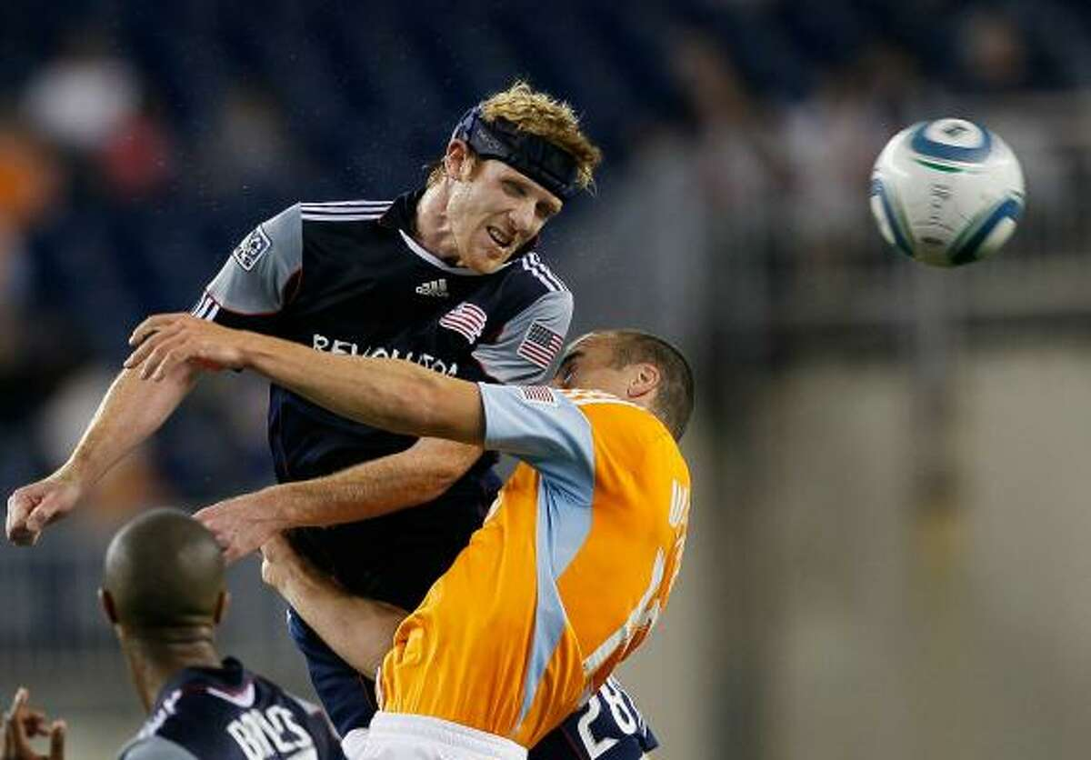 New England's Pat Phelan heads the ball away his net against the defense of Cam Weaver.
