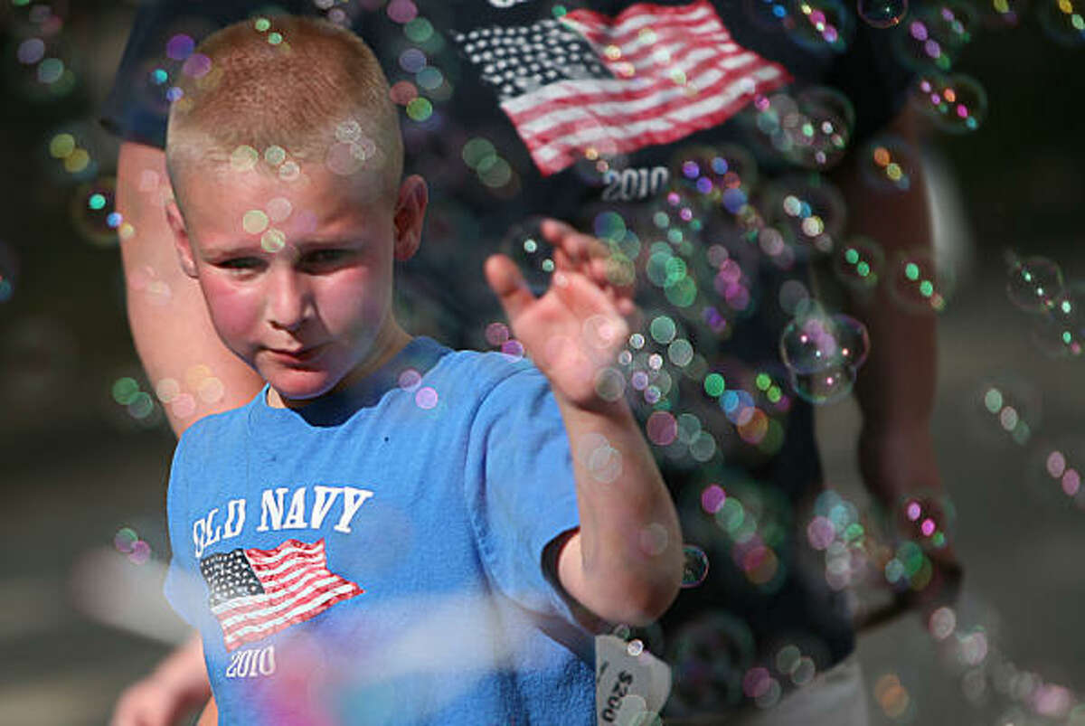 Brice Hart, 6, plays with bubbles as his family walks along the booths at the Freedom Over Texas concert and firework show presented by Shell on Sunday, July 4, 2010, in Houston. Texas singer-songwriter Pat Green headlined the annual event with his performance culminating in the nation's largest land-based fireworks show. Admission to the event is FREE with the donation of one canned item per person to the Houston Food Bank.