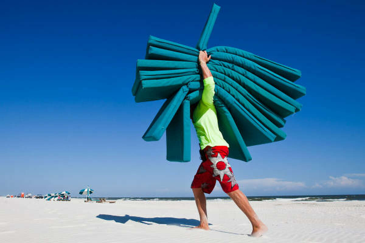 Beach attendant Hampton Honeycutt, 21, of Perdido Beach Services, puts away unused lounge cushions and beach umbrellas on Saturday, July 3, 2010, in Orange Beach, Ala. Business on the beach was off by at least 70 percent from what it was the previous Independence Day weekend Honeycutt said. Beach regulars said the normally busy holiday weekend looked more like 'snowbird season.'