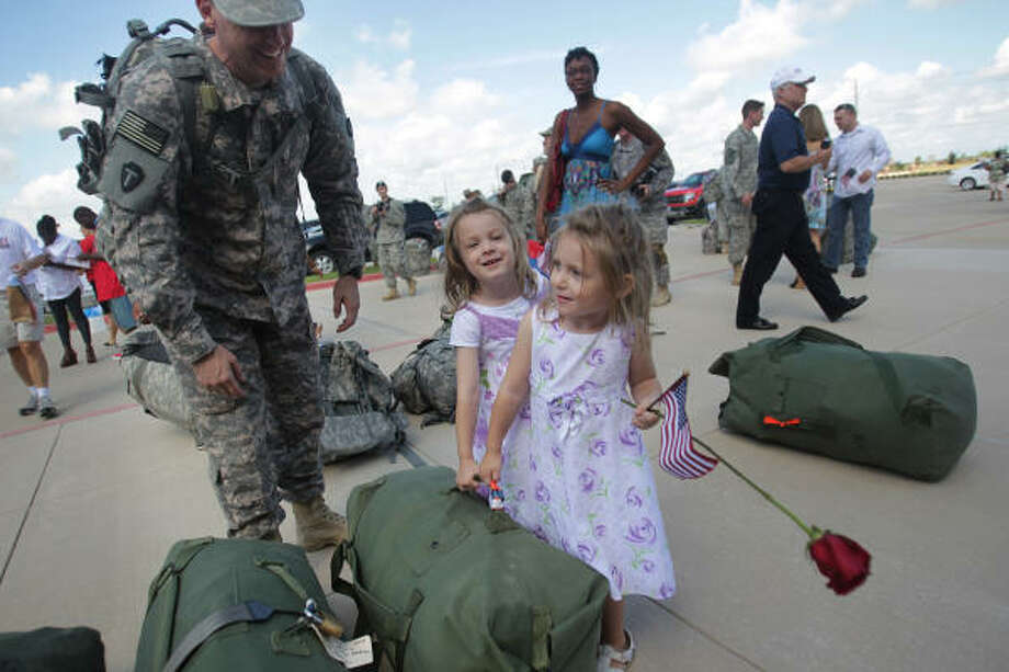 """Carry daddy's bag"" says Chaplain Lt. Col. John Laing in a joking manner to daughters Sydney and Sophia Laing as he got ready to go home with his family after the Texas National Guards HHC-72nd Infantry Brigade Combat Team's welcome home ceremony at the Cypress Ranch High School. The HHC-72nd IBCT company completed a 9-month deployment in Iraq. Photo: Mayra Beltran, Chronicle"