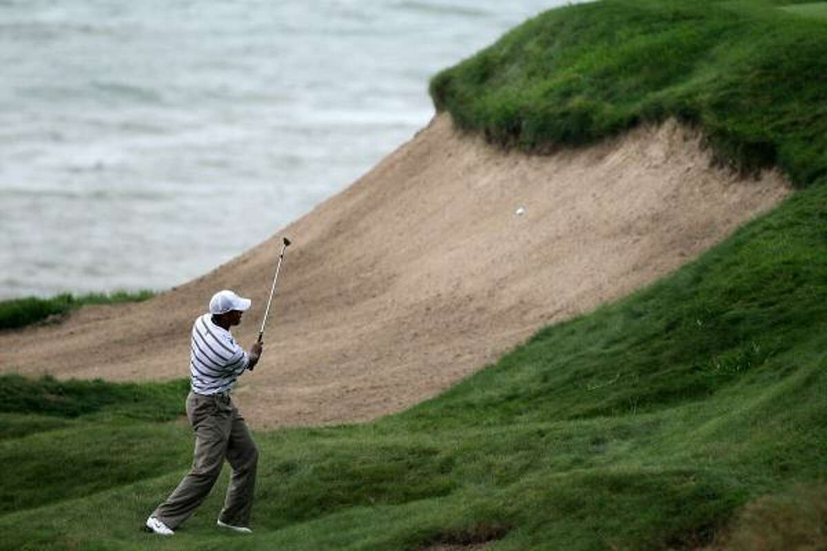 Tiger Woods plays a shot on the third hole.