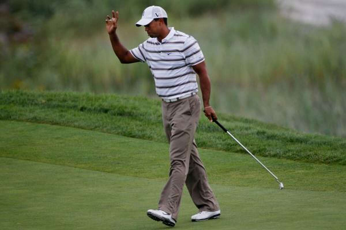 Tiger Woods waves to the gallery on the second green.