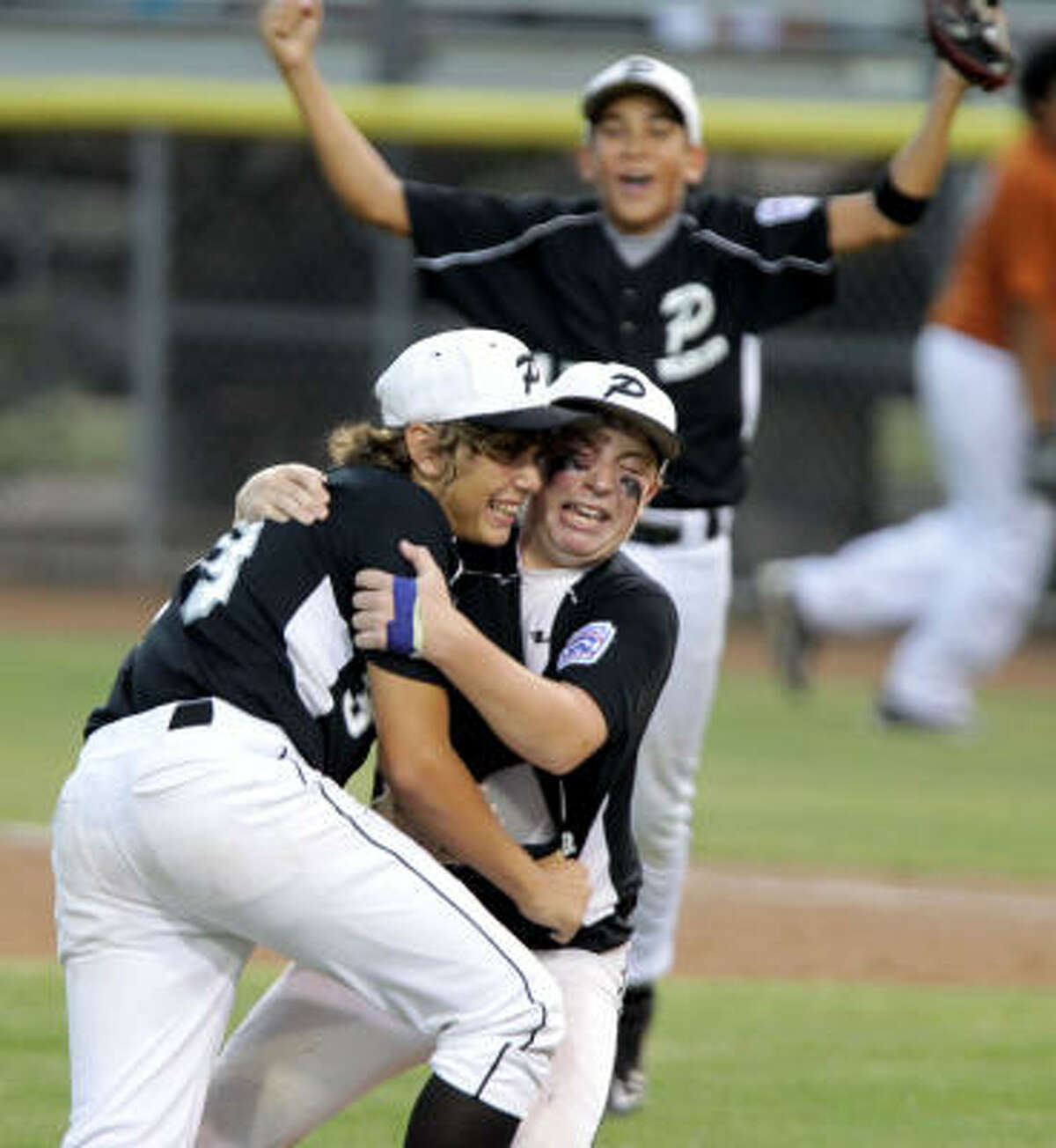 Pearland starting pitcher Beau Orlando, right, and reliever Mason Van Noort celebrate after the game's final out is recorded.