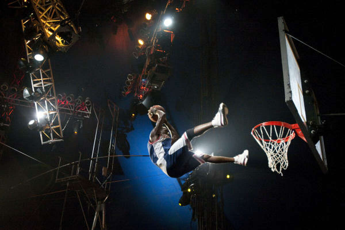 Cedric Abayi tries to complete an acrobatic dunk during the UniverSoul Circus. The circus has a hip hop atmosphere with urban dancing, entertainment, including traditional circus acts.