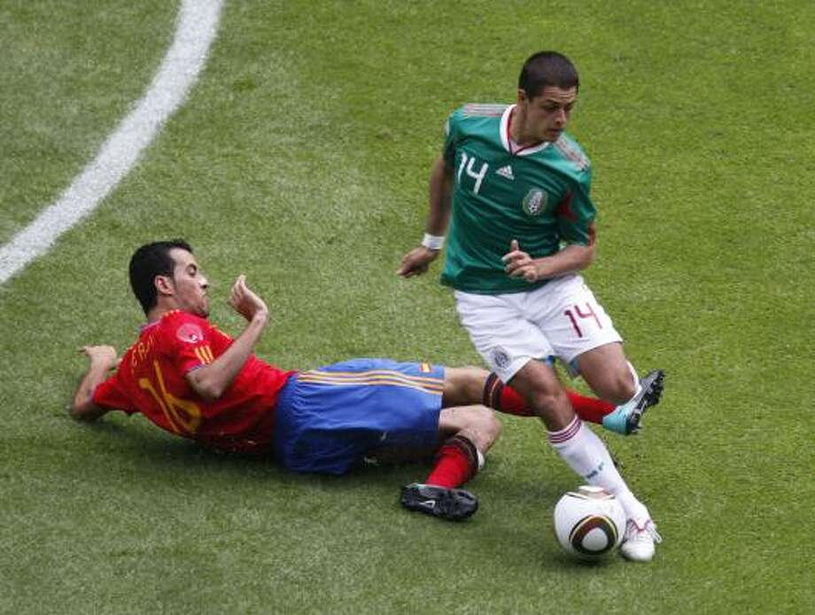 "MEXICO 1, SPAIN 1Mexico's Javier ""Chicharito"" Hernandez goes around Spain defender Sergio Busquets. Hernandez scored Mexico's goal in the  12th minute. Photo: Eduardo Verdugo, AP"