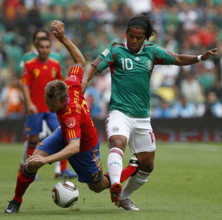 Spain's Ignacio Monreal, left, fights for the ball with Mexico's Giovani Dos Santos. Photo: Claudio Cruz, AP
