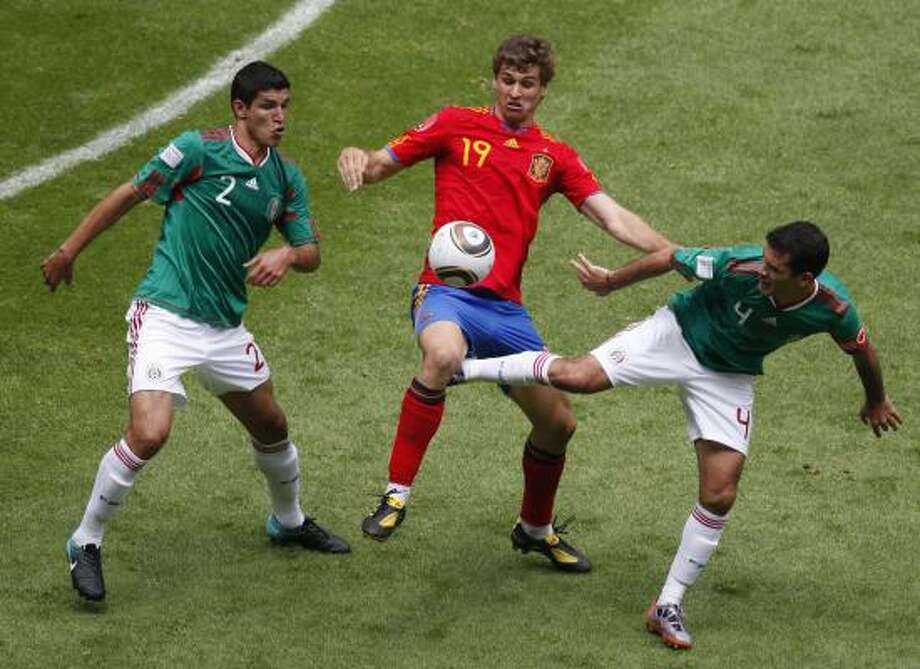 Mexico's Francisco Rodriguez, left, and Rafael Marquez, right, fight for the ball with Spain's Fernando Llorente. Photo: Eduardo Verdugo, AP