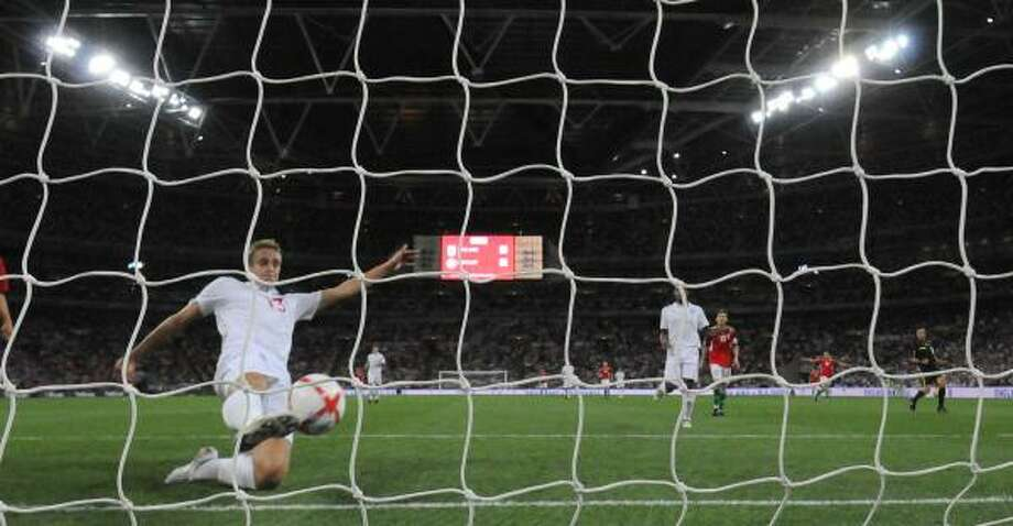 England's Michael Dawson unsuccessfully attempts to keep the ball out of his own goal. Photo: Tom Hevezi, AP