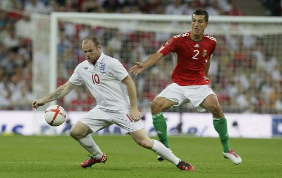 England's Wayne Rooney, left, is defended by  Hungary's Zoltan Liptak. Photo: Kirsty Wigglesworth, AP