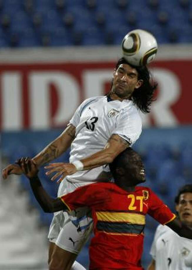 URUGUAY 2, ANGOLA 0Uruguay's Sebastian Abreu, heads the ball over Angola's Dani at Restelo Stadium in Lisbon, Portugal. Photo: Francisco Seco, AP