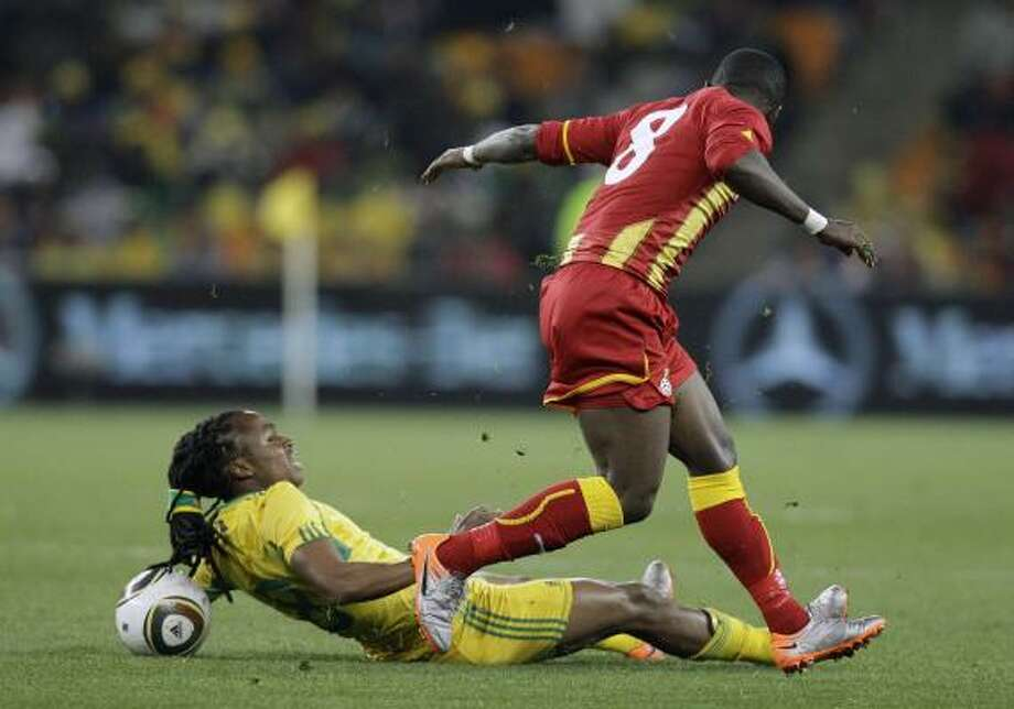 SOUTH AFRICA 1, GHANA 0 South Africa's Siphiwe Tshabalala, left, slides into Ghana's Emmanuel Agyemang Badu at Soccer City stadium in Johannesburg, South Africa. A goal by Katlego Mphela gave South Africa the victory. Photo: Themba Hadebe, AP