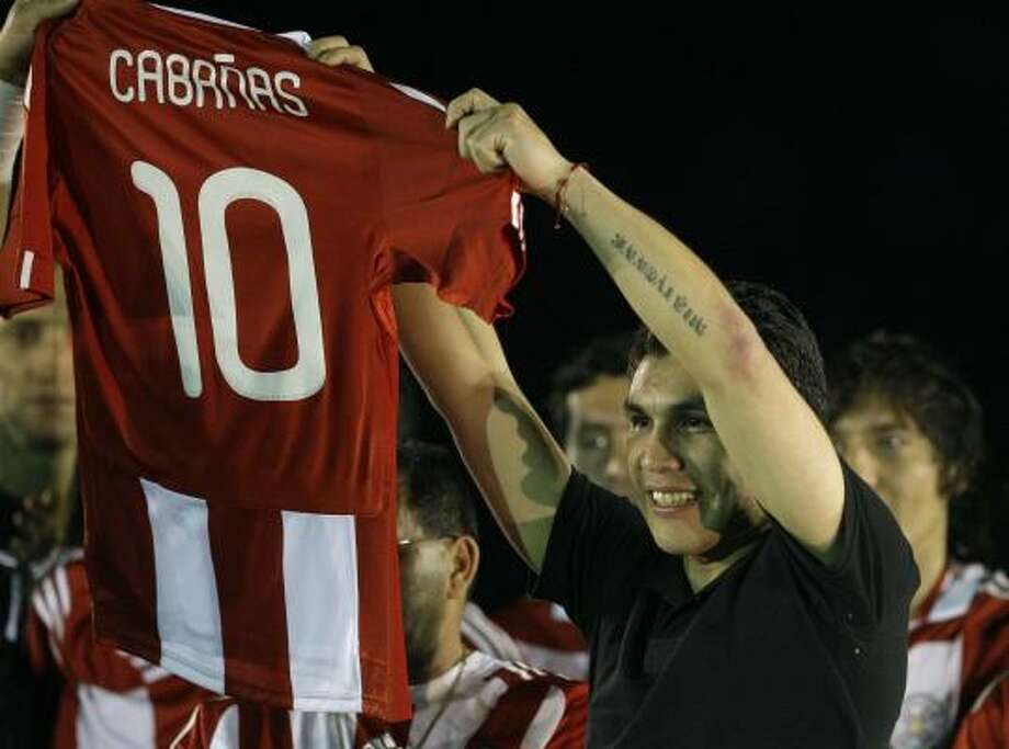 Salvador Cabañas holds up his official jersey as he is honored by Paraguayan teammates before a match with Costa Rica. Cabañas, who would have been a key member of the World Cup team, survived a gunshot wound to the head on Jan. 25 in a bar in Mexico City and has been undergoing treatment at a rehabilitation clinic in Buenos Aires,  Argentina. Photo: Jorge Saenz, AP