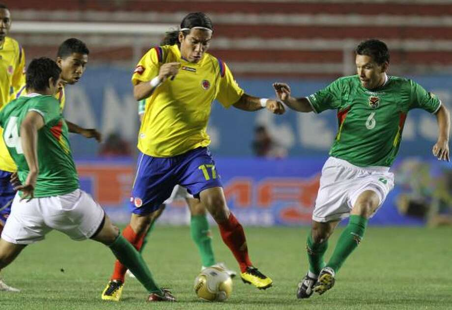 BOLIVIA 1, COLOMBIA 1 Colombia's Dayro Moreno, center, tries to work his way through the defense of Bolivia's Ignacio Garcia, left, and Nicolas Suarez in La Paz, Bolivia. Photo: Juan Karita, AP