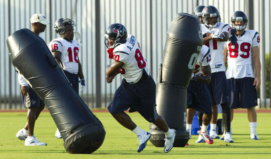 Texans wide receiver Andre Johnson (80) runs through a pair of blocking dummies during drills. Photo: Brett Coomer, Chronicle