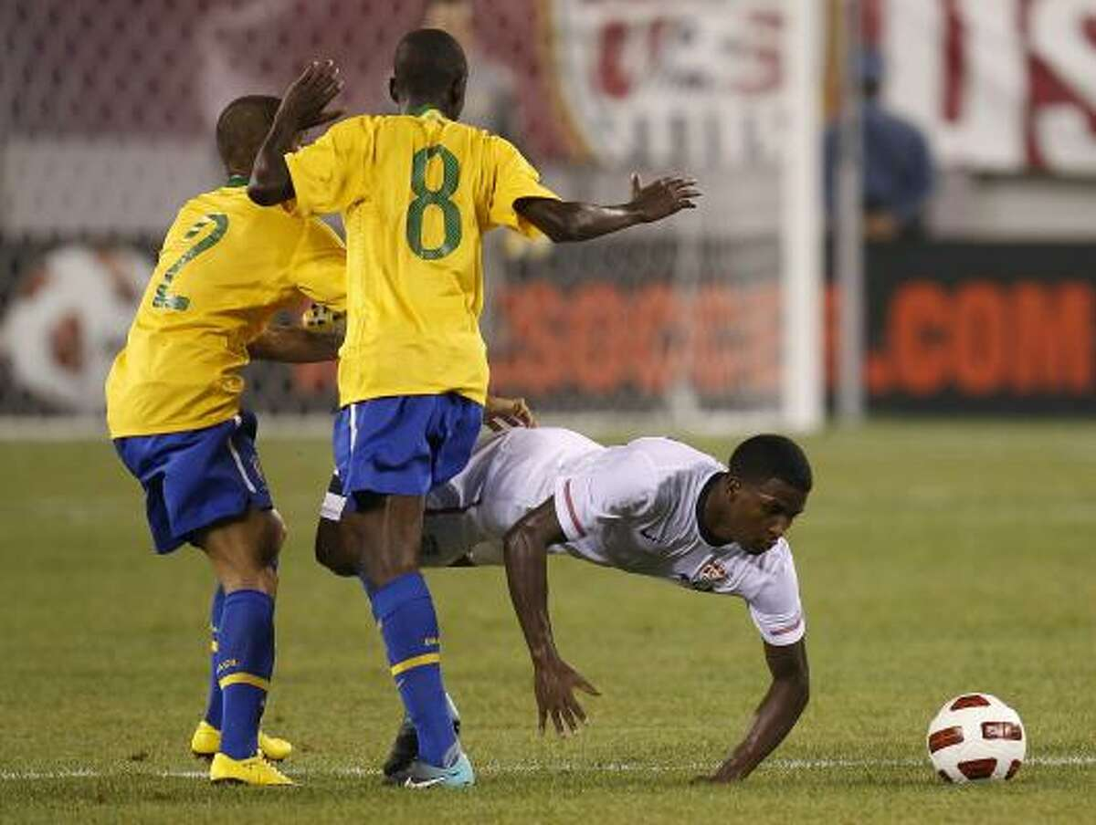 Maurice Edu of the U.S. loses his footing in front of Brazil's Dani Alves, left, and Ramires during Tuesday's match.
