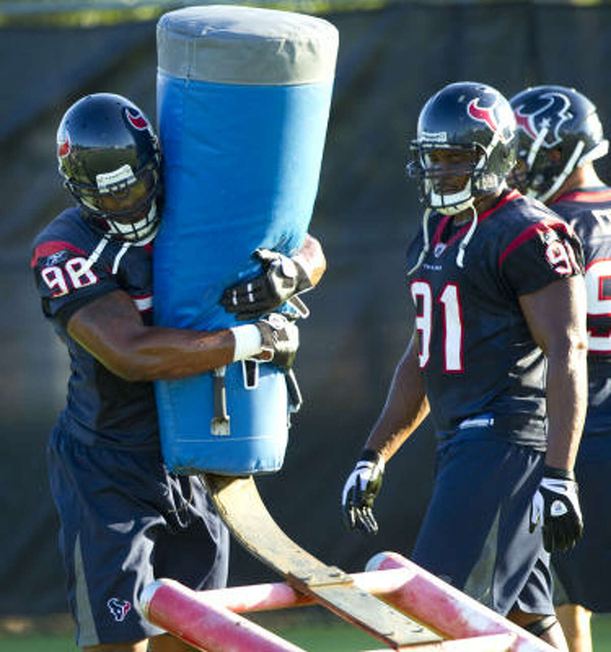Texans defensive end Mario Williams (90) hits a blocking sled with Amobi Okoye (91) and Shaun Cody waiting for their turn.