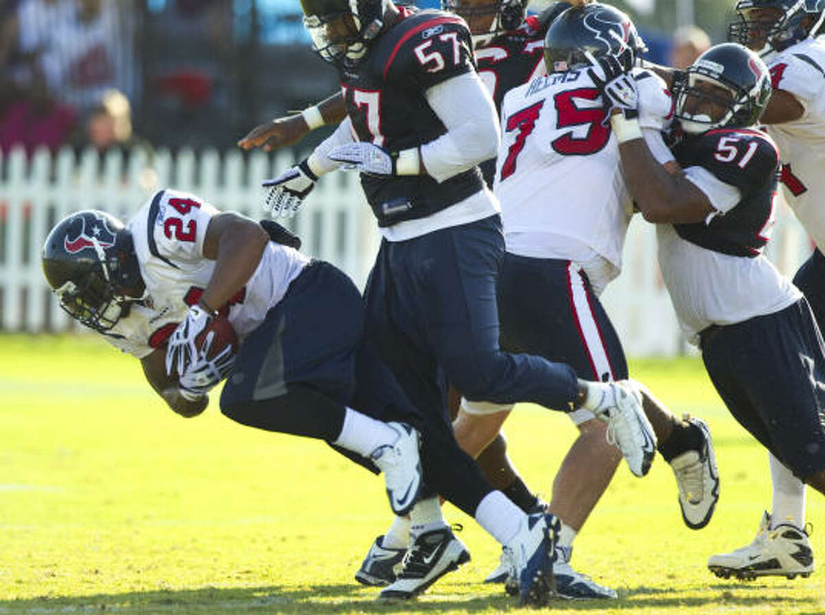 Texans running back Jeremiah Johnson (24) runs the ball past linebacker Kevin Bentley (57), Brett Helms (75) and linebacker Darryl Sharpton (51).