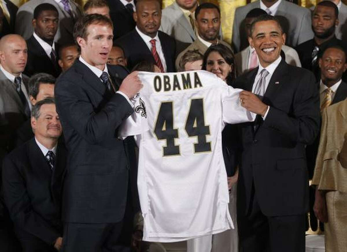 New Orleans Saints quarterback Drew Brees and President Barack Obama hold a personalized jersey in the East Room of the White House.