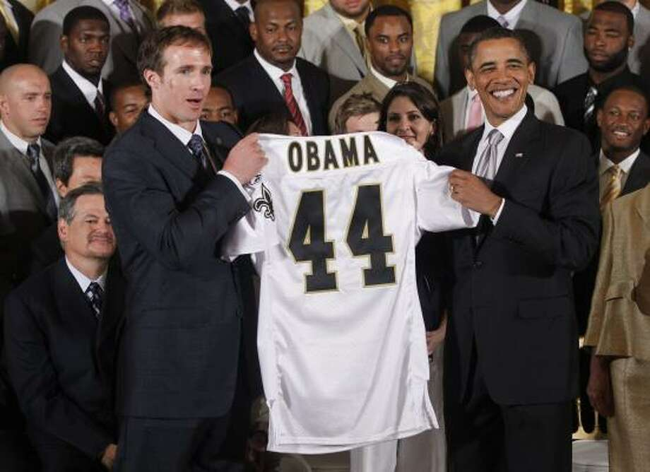 New Orleans Saints quarterback Drew Brees and President Barack Obama hold a personalized jersey  in the East Room of the White House. Photo: Charles Dharapak, AP