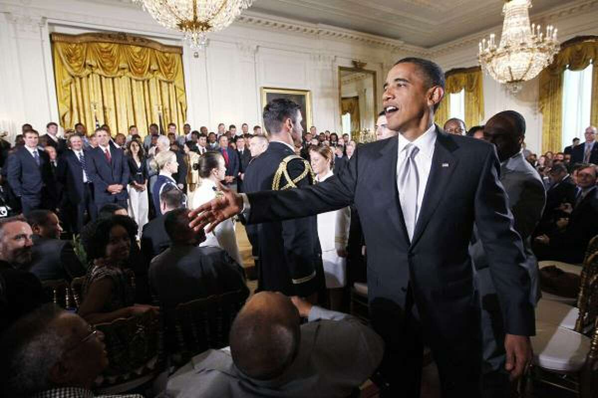President Barack Obama greets guests in the East Room, where he honored the 2009 NFL champions.