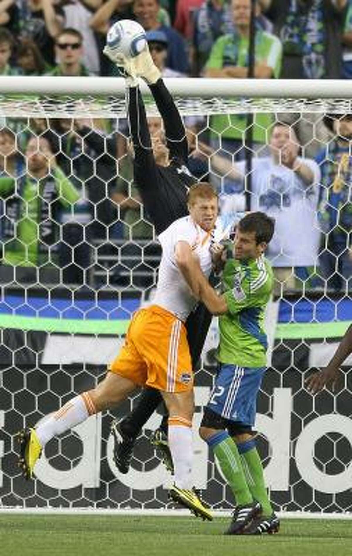Sounders goalkeeper Kasey Keller blocks a shot in front of Sounders defender Nathan Sturgis and Dynamo defender Andrew Hainault.