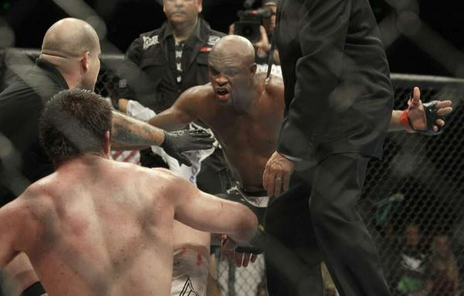 Anderson Silva, center, celebrates in front of Chael Sonnen after submitting Sonnen in the fifth round to retain the middleweight title. Photo: Jeff Chiu, AP