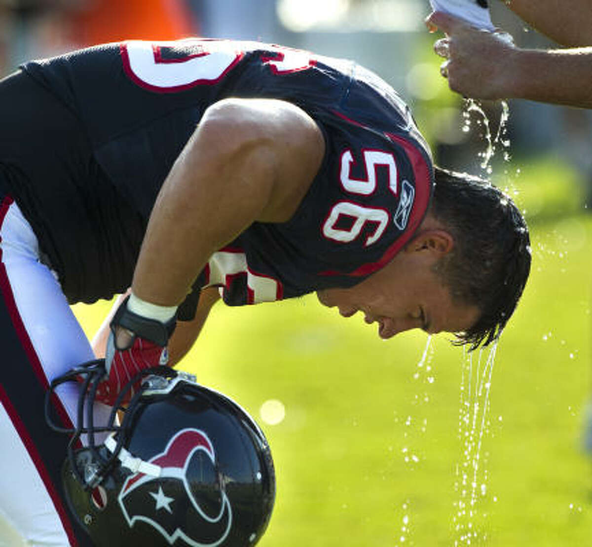 Linebacker Brian Cushing has water splashed on his head between drills.