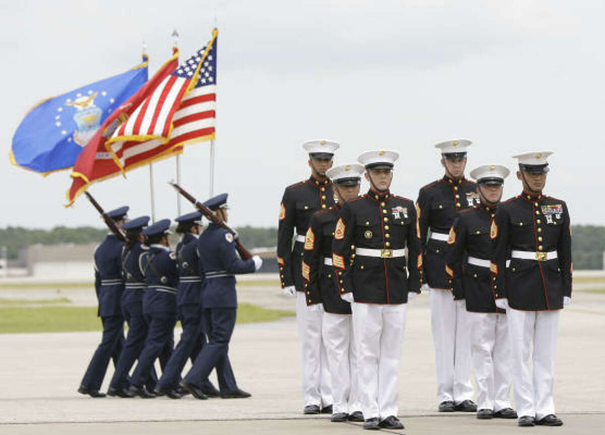 Marines stand at attention after carrying the casket of Lance Cpl. Shane R. Martin of Spring to the hearse as the Klein Collins High School Air Force Jr. ROTC color guard marches past.