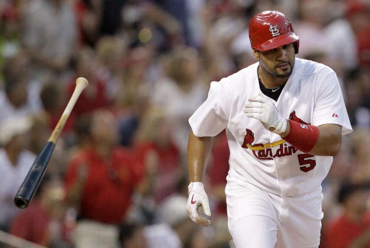 Cardinals first baseman Albert Pujols tosses aside his bat after hitting a three-run home run.