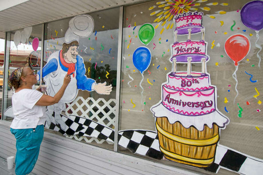 MOELLER'S BAKERY: Artist Mary Coronis prepares the windows at Moeller's Bakery for the celebration of its 80th anniversary on August 14.  Coronis has been painting holiday decorations on the windows for years. Photo: R. Clayton McKee, For The Chronicle