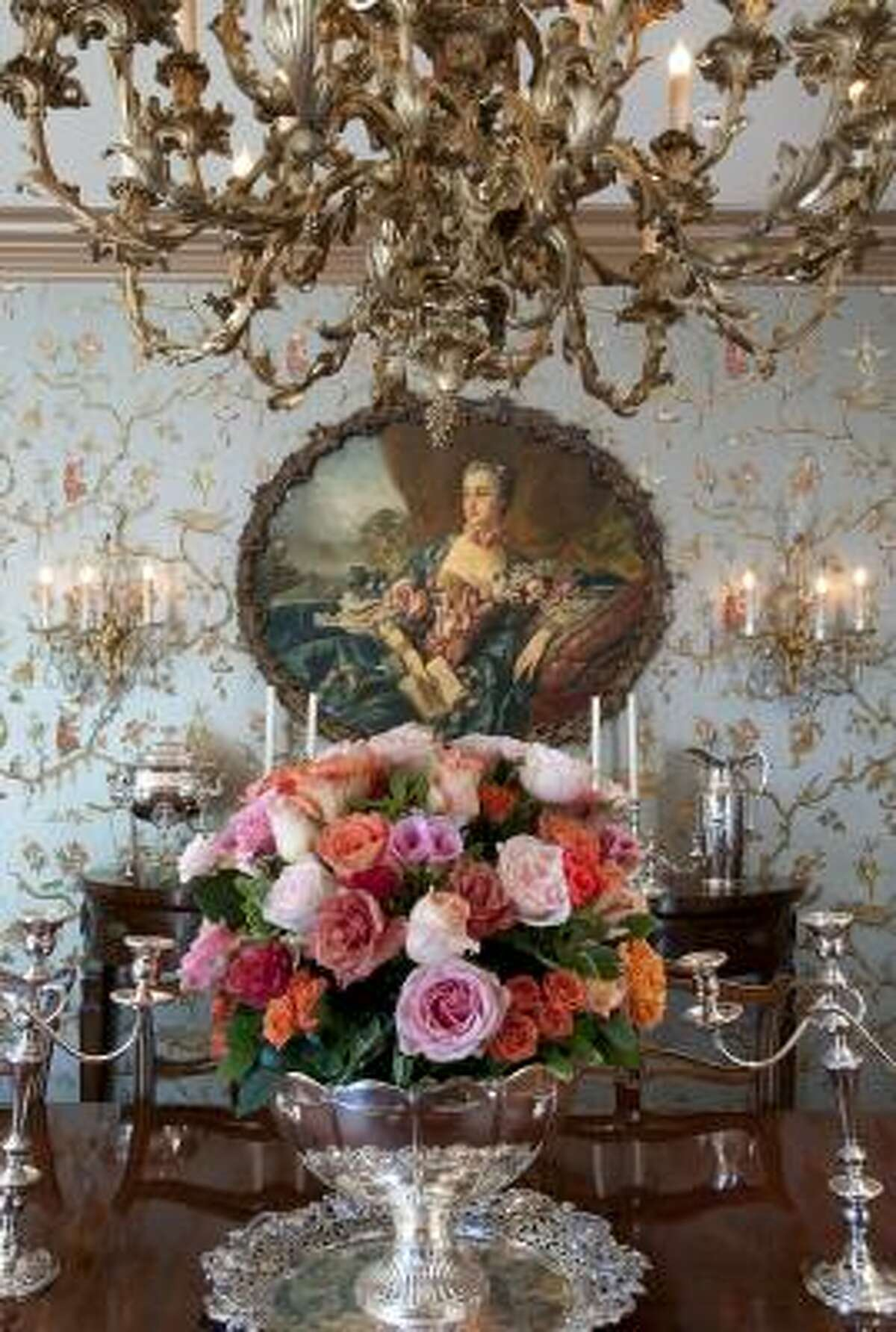 """TRADITIONAL OPULENCE: Family heirlooms have pride of place in the formal dining room, which also sparkles with Schumacher's sumptuous """"Jester"""" wallpaper. The owners purchased the painting at auction and brought the chandelier from a previous home. Floral arrangements throughout by Mason Floral."""