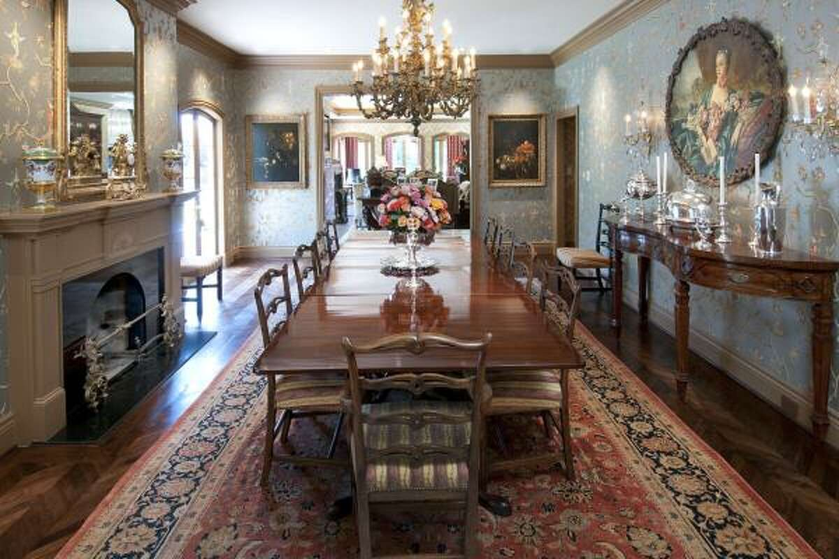 """READY FOR ROYALTY: The exuberant dining room flows into a spacious great room and large breakfast room, with views of the pool and gardens. The chair seats are covered in Schumacher's """"Laurel Stripe."""""""