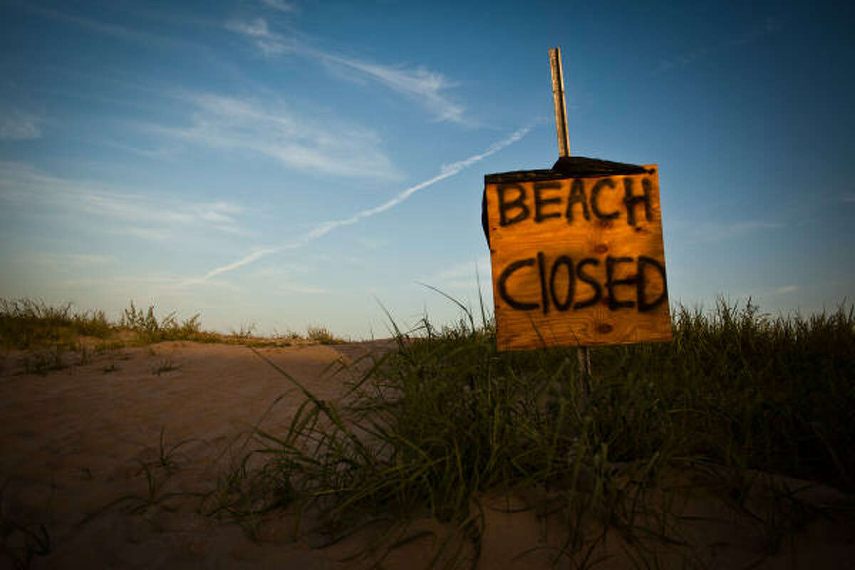 A makeshift sign warns of the closed beach in Grand Isle.