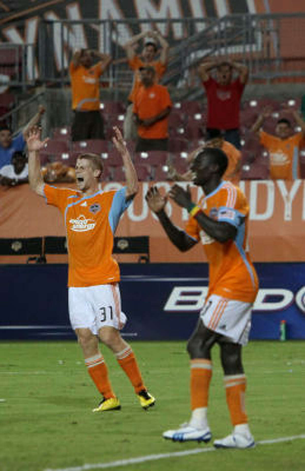 Dynamo defender Andrew Hainault and forward Dominic Oduro react to midfielder Lovel Palmer missing a shot in the 90th minute.