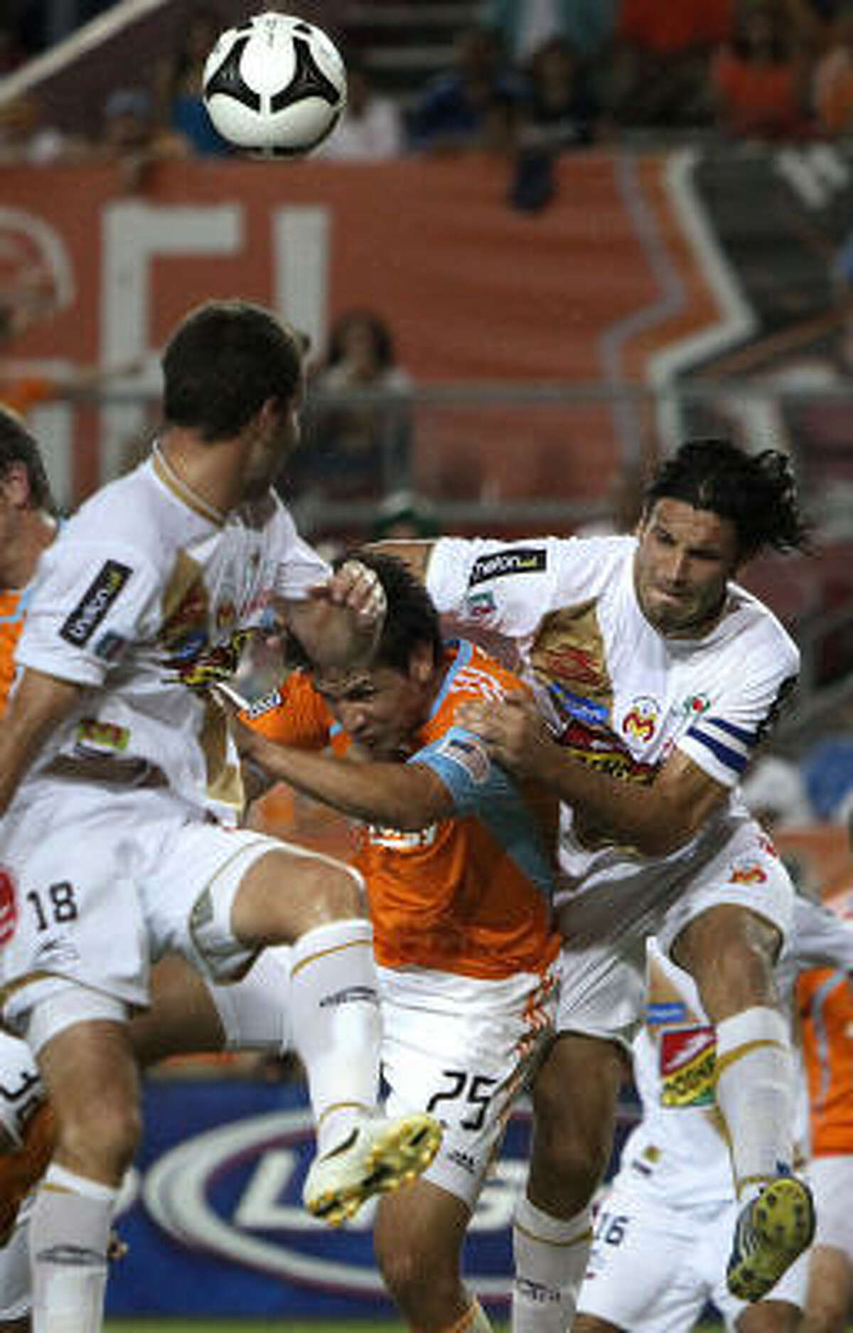 Dynamo forward Brian Ching battles for the ball against Morelia's Luis Gabriel Rey and Mauricio Romero.