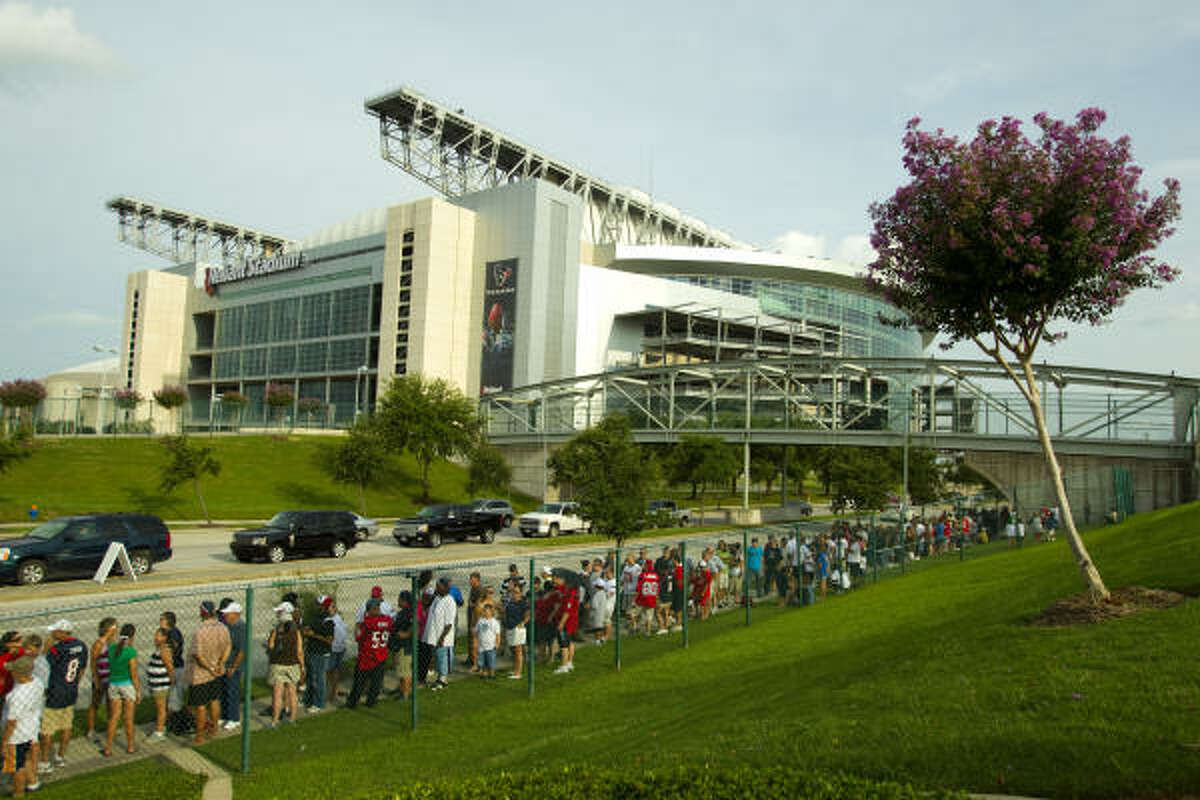 Texans fans line up outside the Texans training facility across the street from Reliant Stadium as they wait to attend practice.