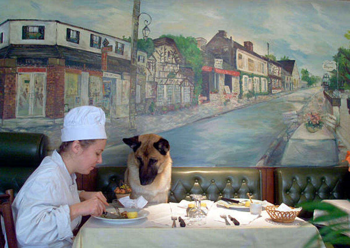 French chef Delphine Grapperon has lunch as her dog Maude looks on at her Barbizon restaurant Le Royal, with a painting of the town's main street in background, in France.