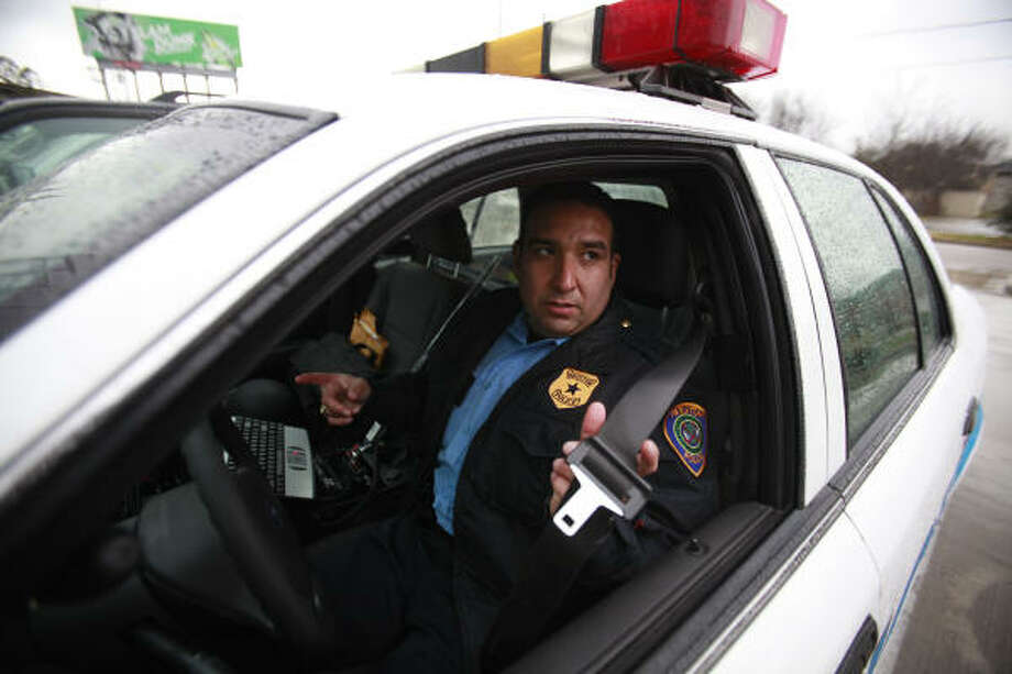 HPD Sgt. A.J. Gonzales demonstrates how a buckled-in officer can get tangled up in a seat belt in an emergency. Police officials, however, encourage officers to wear belts whenever driving. Photo: Mayra Beltran, Chronicle