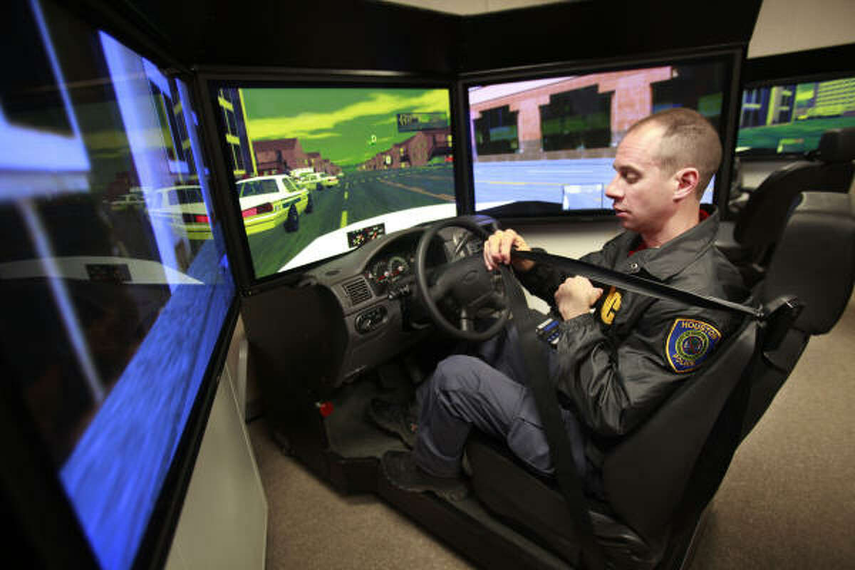 Officer Scott Dexter belts in as he prepares to demonstrate the driving simulator at the Houston Police Academy.