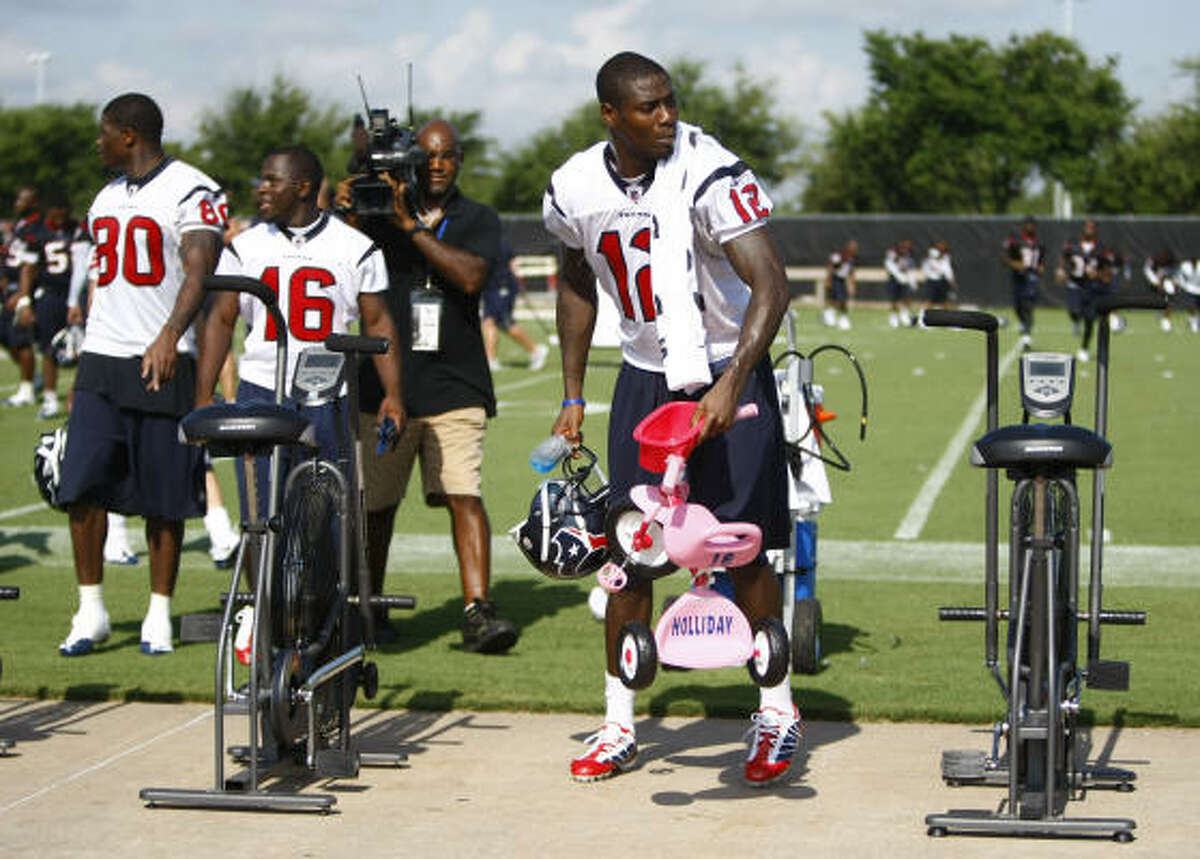 Texans wide receiver Jacoby Jones (12) picks up a little pink tricycle next to a row of stationary bikes that wide receiver Trindon Holliday was forced to bring to practice as part of rookie hazing.