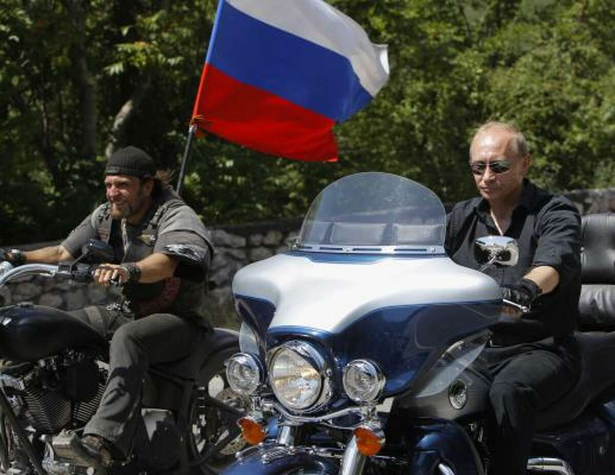 VLADIMIR PUTIN : Russia's Prime Minister Vladimir Putin, right, rides Harley Davidson Lehman Trike as he arrives for the meeting with Russian and Ukrainian motorbikers at their camp near Sevastopol in Ukraine's Crimea Peninsula, Saturday, July 24, 2010. Russian flag is in the background. Putin has lept on a Harley Davidson and roared into a international biker convention in southern Ukraine. Around 5,000 bikers from Europe and beyond are gathered in Sevastopol for the annual festival on Ukraine's Crimea peninsula.