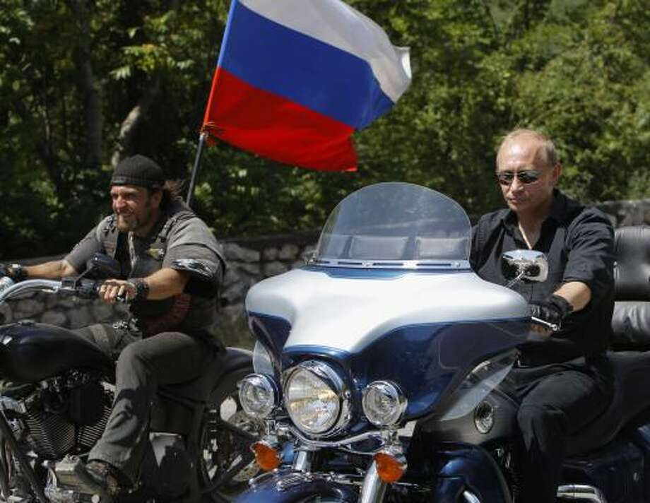 VLADIMIR PUTIN: Russia's Prime Minister Vladimir Putin, right, rides Harley Davidson Lehman Trike as he arrives for the meeting with Russian and Ukrainian motorbikers at their camp near Sevastopol in Ukraine's Crimea Peninsula, Saturday, July 24, 2010. Russian flag is in the background. Putin has lept on a Harley Davidson and roared into a international biker convention in southern Ukraine. Around 5,000 bikers from Europe and beyond are gathered in Sevastopol for the annual festival on Ukraine's Crimea peninsula. Photo: Sergei Karpukhin, AP
