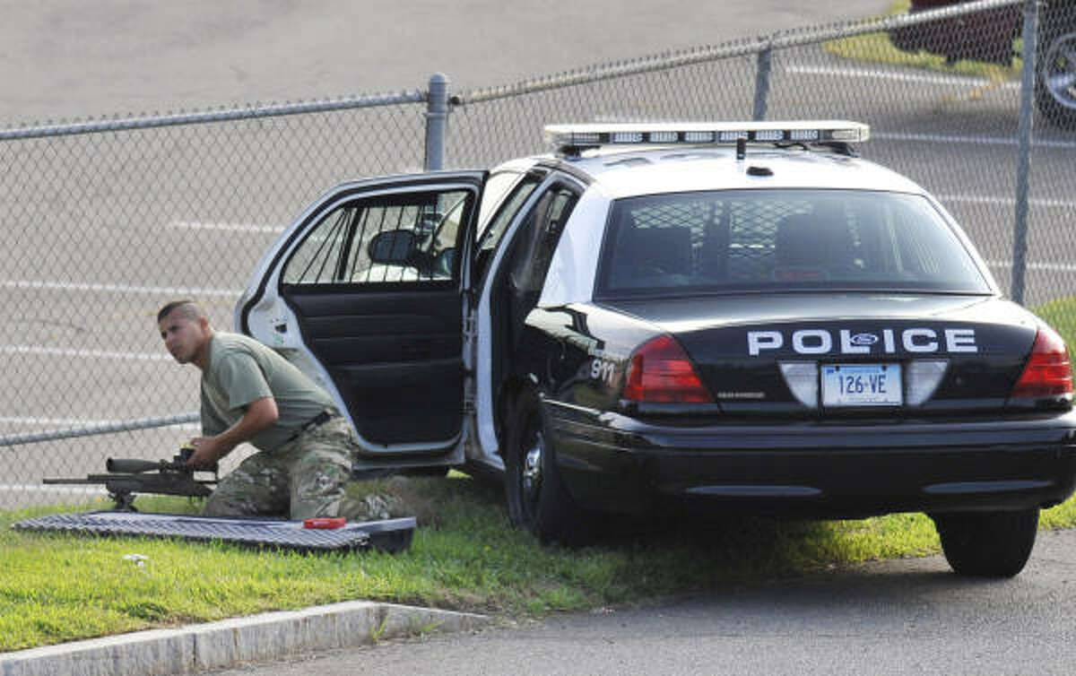 A police officer sets up nearby the Hartford Distributors, Inc., in Manchester, Conn., Tuesday, Aug. 3, 2010.
