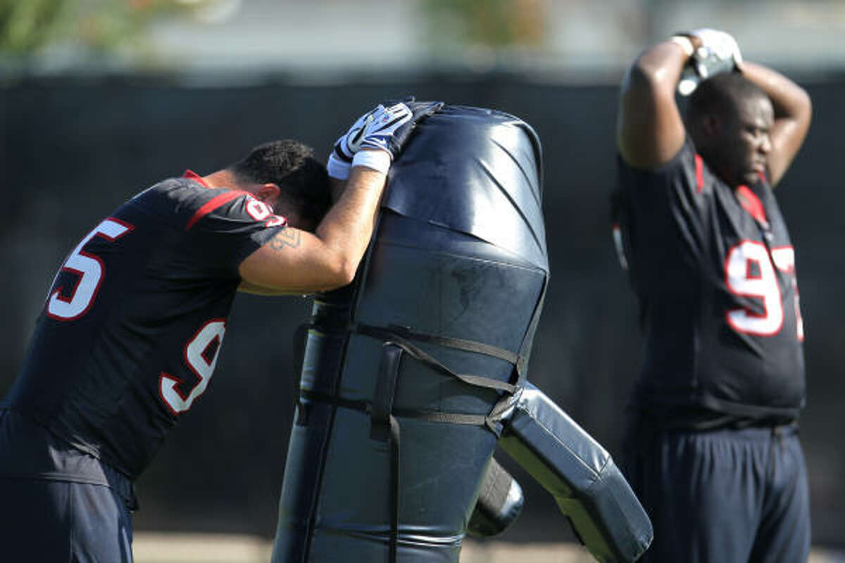 Texans defensive tackles Shaun Cody (95) and Frank Okam (97) rest between drills during Tuesday's fifth day of training camp at Methodist Training Center.