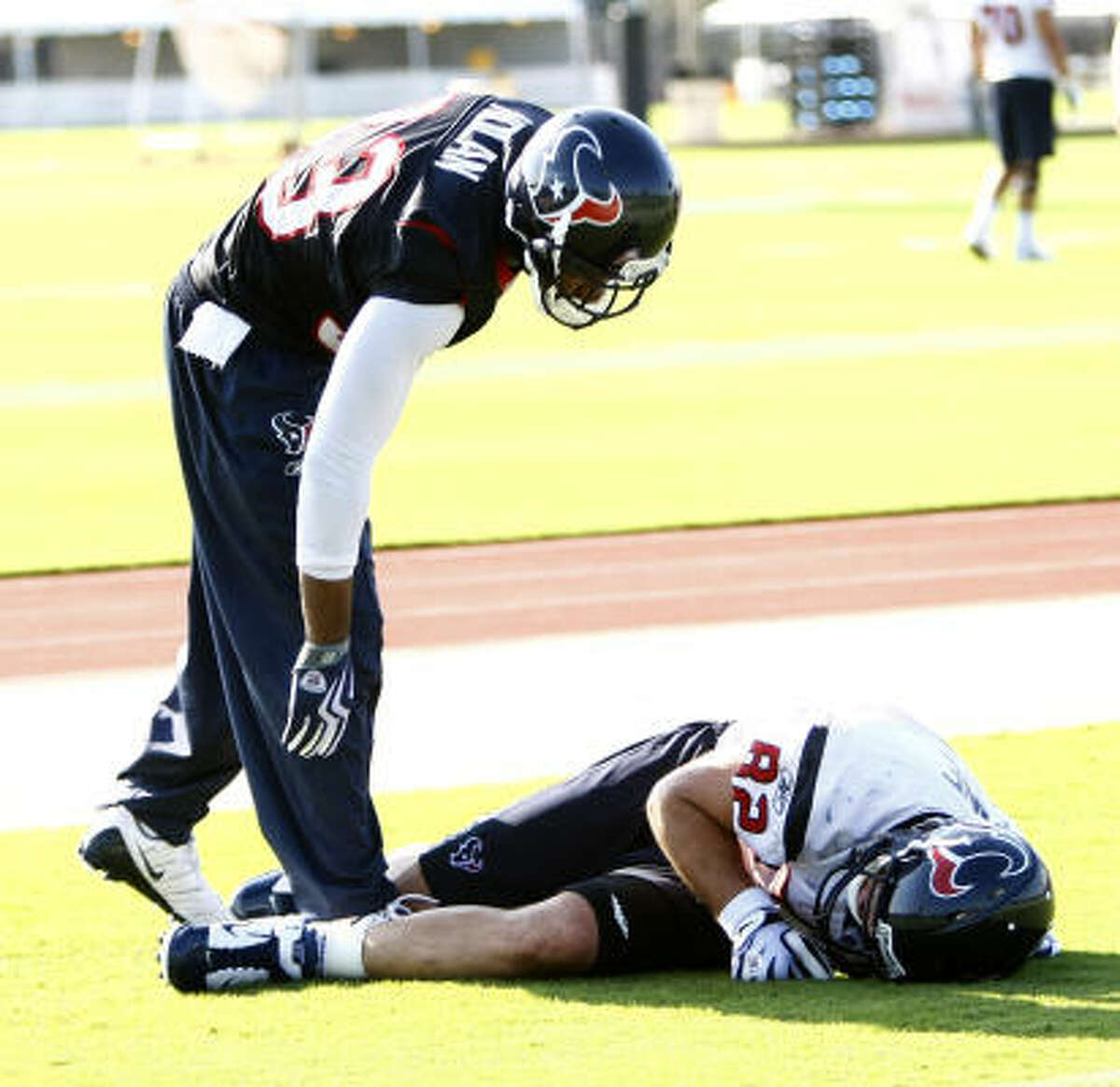 Texans tight end Derek Fine lies on the ground after getting injured on a play with teammate Troy Nolan.