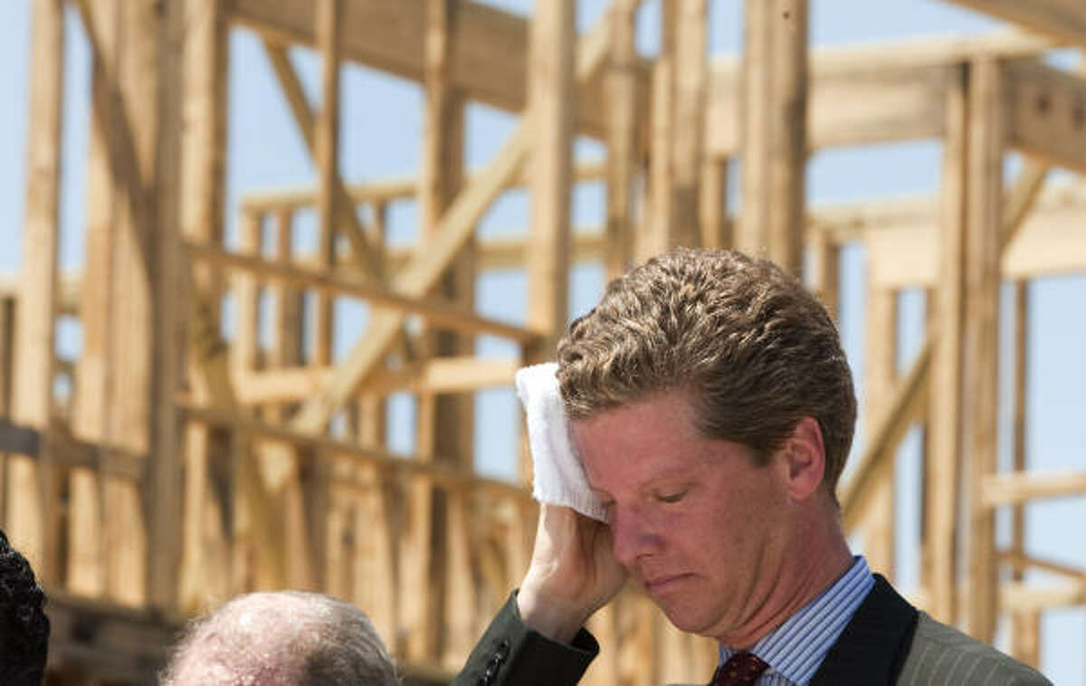 U.S. Housing and Urban Development Secretary Shaun Donovan wipe sweat from his brow while on a tour of the Kennedy Place development in Houston.